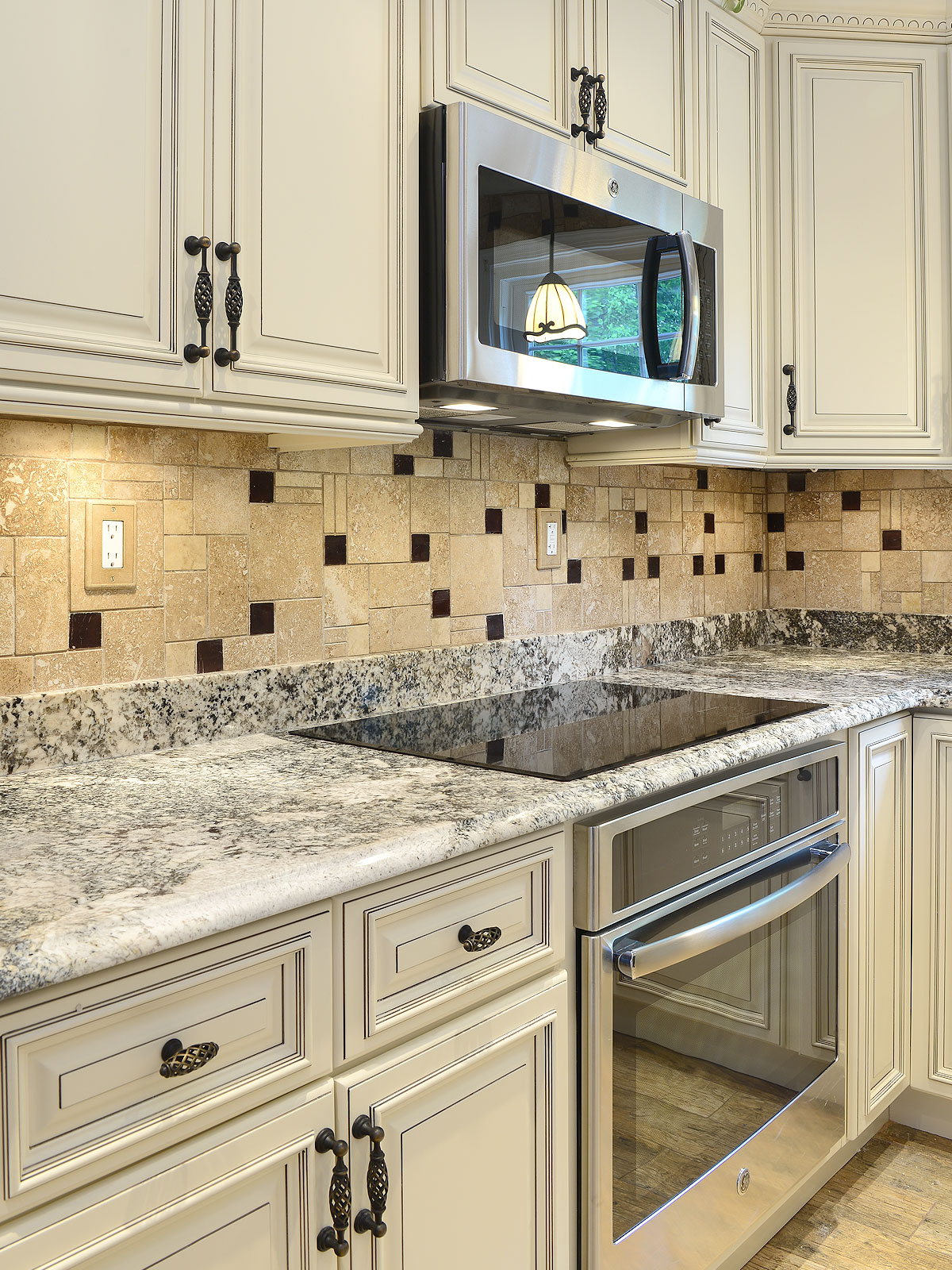Beige cabinets granite countertop travertine glass backsplash tile BA1043