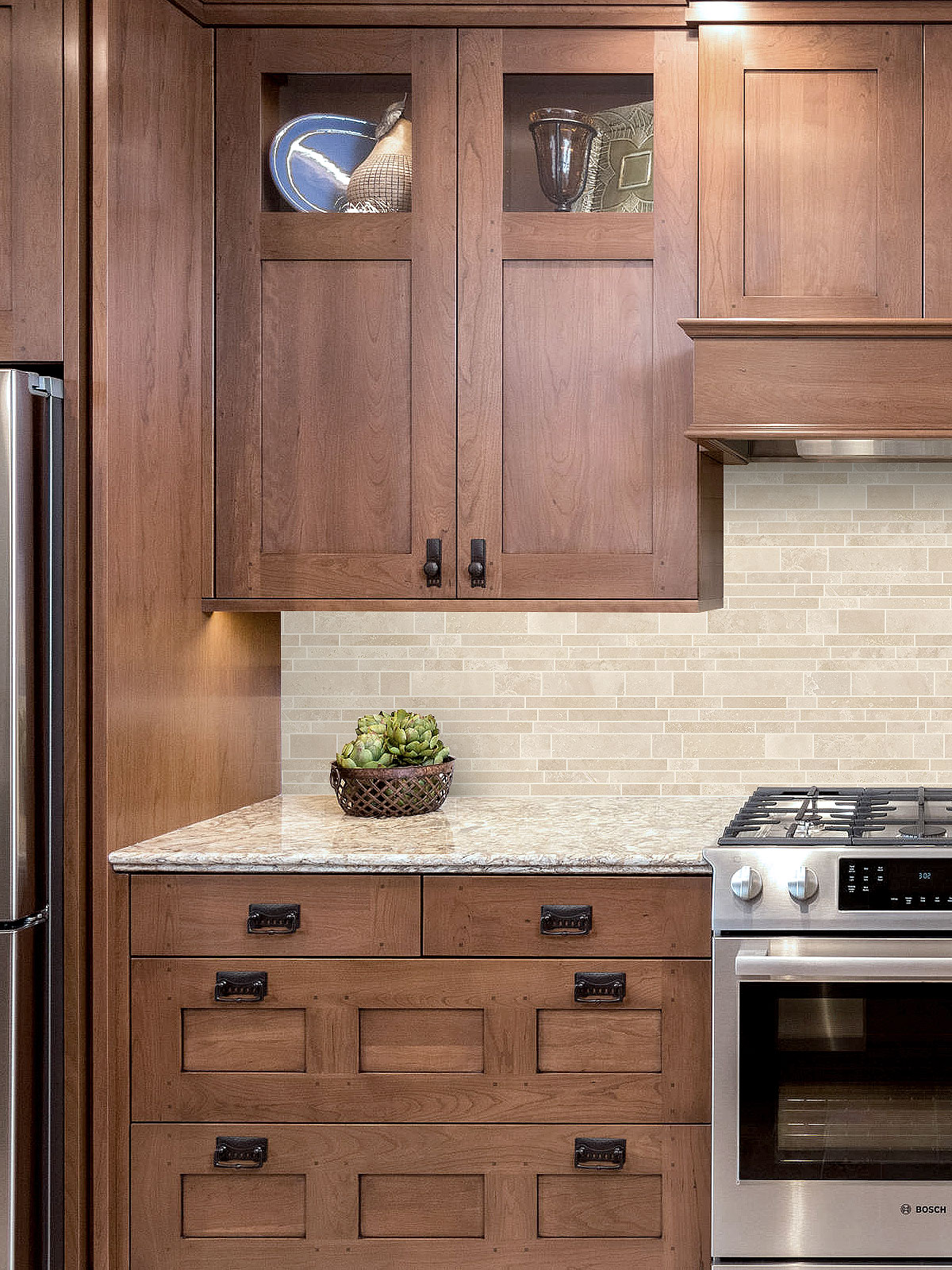 Brown cabinets gold granite countertop travertine backsplash tile